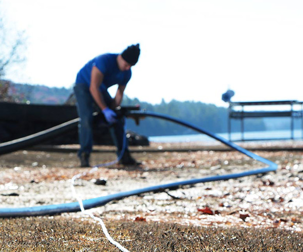 Contractor holding Polyethylene Pipe outdoors near a lake