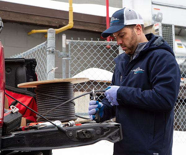 Contractor cutting self-regulating heat trace cable from reel on tailgate