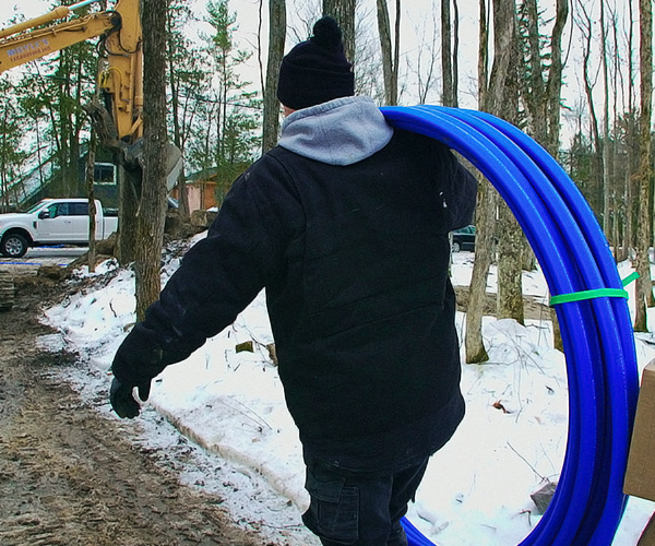 Contractor carrying water line freeze protection system over shoulder to job site